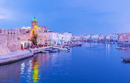 BIZERTE, TUNISIA - SEPTEMBER 4, 2015: The medieval cityscape on blue hour with a view on old port, rampart of Ksiba fortress and minaret of the mosque, reflected in dark blue waters, on September 4 in Bizerte