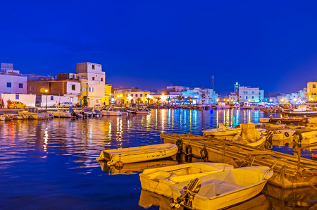 BIZERTE, TUNISIA - SEPTEMBER 4, 2015: Watch the evening city from the port with many moored fishing boats and bright city lights, reflected on water surface, on September 4 in Bizerte Publikacyjne