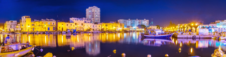 BIZERTE, TUNISIA - SEPTEMBER 4, 2015: Panorama of evening port, with many moored boats and illuminated buildings, reflected on water surface, on September 4 in Bizerte