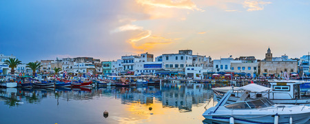 BIZERTE, TUNISIA - SEPTEMBER 4, 2015: Panorama of port with many moored fishing boats, cafes and vintage edifices on cloudy sunset, on September 4 in Bizerte