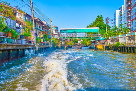 BANGKOK, THAILAND - APRIL 24, 2019: Saen Saep canal leads across scenery residential neighborhoods along shabby slums, depicting the life of ordinary people, on April 24 in Bangkok