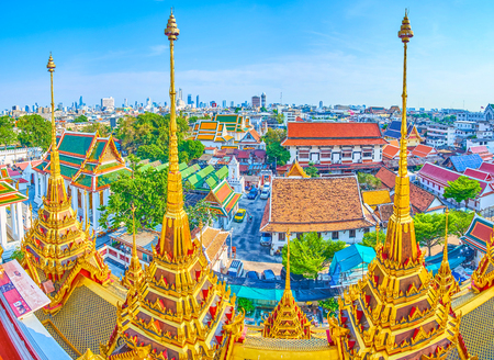 BANGKOK, THAILAND - APRIL 24, 2019: The large Wat Ratchanatdaram complex with numerous edifices of different purposes and golden spires of Loha Prasat shrine, dominating over the cityscape of old town, on April 24 in Bangkok