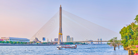 BANGKOK, THAILAND - APRIL 24, 2019: The scenic view on rivers of Chao Phraya river with stone Rama XIII Bridge and fasm moving tourist ship, on April 24 in Bangkok