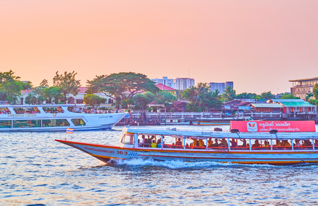 BANGKOK, THAILAND - APRIL 24, 2019: River cruises are the best way to explore the citylife from one of the most busy thoroughfare, the Chao Phraya river, on April 24 in Bangkok