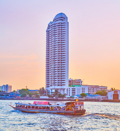 BANGKOK, THAILAND - APRIL 24, 2019: Evening is the best time to explore the activity on Chao Phraya river, the boats move fast, transporting passengers from pier to pier,  on April 24 in Bangkok