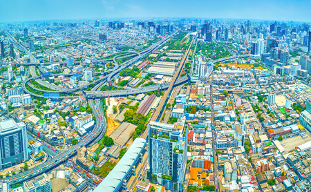 BANGKOK, THAILAND - APRIL 24, 2019: Panorama of modern city with high edifices and large highway intersection, on April 24 in Bangkok