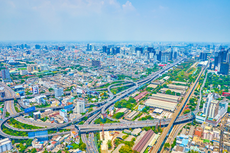 BANGKOK, THAILAND - APRIL 24, 2019: The scenic aerial view from Baiyoke Tower II on modern city with highway interchange with numerous grade separations of the routes, on April 24 in Bangkok