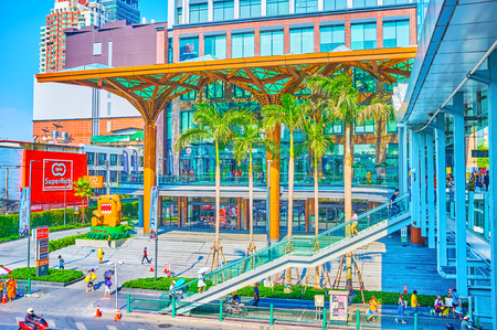 BANGKOK, THAILAND - APRIL 24, 2019:  The modern department store with glass facade and large canopy connects with pedestrian skywalk that connects main stores of shopping zone, on April 24 in Bangkok Редакционное