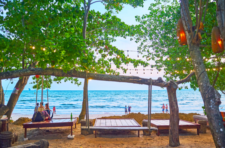 AO NANG, THAILAND - APRIL 25, 2019: Enjoy romantic evening in nice lounge cafe, located on the beach undr the spread trees, on April 25 in Ao Nang