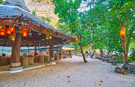 AO NANG, THAILAND - APRIL 25, 2019: The beach bar in wooden hut is decorated with many lanterns, making it cozy and romantic, on April 25 in Ao Nang