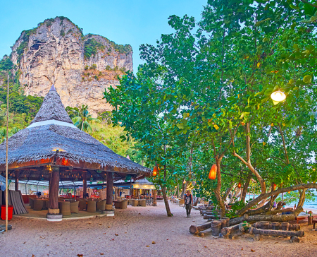 AO NANG, THAILAND - APRIL 25, 2019: The sandy alley through the  evening beach with a view on spread trees and cafe-bar in wooden hut, on April 25 in Ao Nang