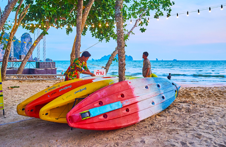 AO NANG, THAILAND - APRIL 25, 2019: The colorful boats for rent on the beach, next to the lounge cafes and bars, on April 25 in Ao Nang