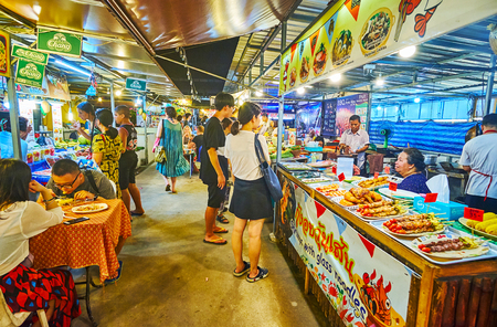 AO NANG, THAILAND - APRIL 25, 2019: The alleyway of food section of the Night Market with stalls, offering tasty dishes, snacks, street foods and cool beverages, on April 25 in Ao Nang