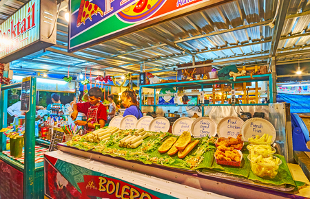 AO NANG, THAILAND - APRIL 25, 2019: The Night Market stall with different sandwiches, rolls, French fries, deep fried chicken and other snacks, on April 25 in Ao Nang