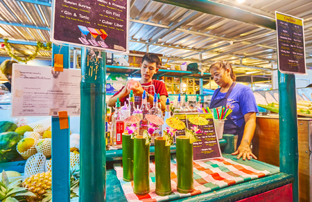 AO NANG, THAILAND - APRIL 25, 2019: The Night Market stall attracts tourists with interesting alcohol cocktails, served in  bamboo glasses with small umbrellas, orchid flowers and pieces of pineapple, on April 25 in Ao Nang Редакционное