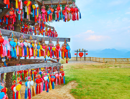 SANTICHON, THAILAND - MAY 5, 2019: Make a wish on Yun Lai viewpoint and hang the small heart on the stand in front of viewing platform with Chinese gate, on May 5 in Santichon Редакционное