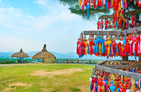 The view on the Yun Lai viewpoint, located on the mountain top with many colorful souvenirs on the foreground, Santichon, Pai, Thailand Редакционное