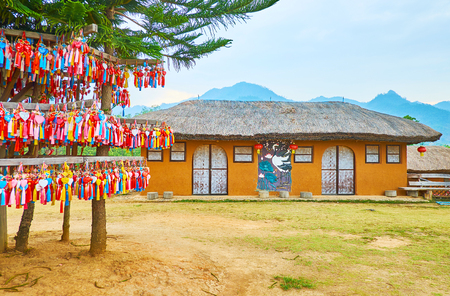 SANTICHON, THAILAND - MAY 5, 2019: Adobe Chinese house at Yun Lai viewpoint, where toutists enjoy the Shan Hills landscapes and leave the colorful souvenirs on the wishing tree, on May 5 in Santichon
