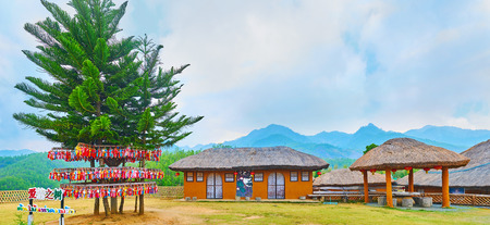 SANTICHON, THAILAND - MAY 5, 2019: Adobe Panorama of the yard of Yun Lai viewpoint with Norfolk Island pines with wishing souvenirs, Chiinese house and small pavilion, on May 5 in Santichon