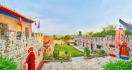 SANTICHON, THAILAND - MAY 5, 2019: Panorama from the rampart of Chinese Yunnan cultural village with a view on buildings with sweeping roofs, small garden, tea house and red lanterns, on May 5 in Santichon