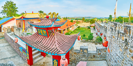 SANTICHON, THAILAND - MAY 5, 2019: Observe the scenic fortress-like architecture of Chinese Yunnan cultural village, ornate gate of the complex is decorated with sweeping roof, gilt dragons and red lanterns, on May 5 in Santichon