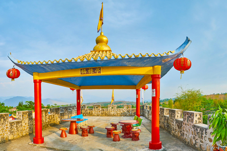 SANTICHON, THAILAND - MAY 5, 2019: Chinese pavilion with sweeping roof, red lanterns and bright red columns on top of the fortress of Yunnan cultural village, on May 5 in Santichon
