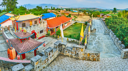 SANTICHON, THAILAND - MAY 5, 2019: The top view on the fortress of Chinese Yunnan cultural village with stone rampart, sweeping roofs and many red lanterns, on May 5 in Santichon