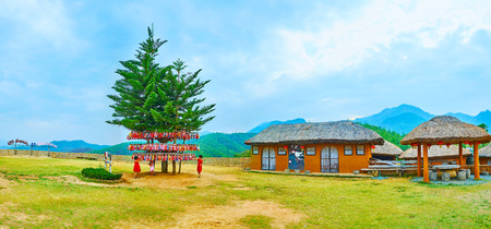 SANTICHON, THAILAND - MAY 5, 2019: Panorama of Yun Lai viewpoint with adobe Chinese houses, pavilions and Norfolk Island pines, surrounded by wishing souvenirs and ribbons, on May 5 in Santichon Редакционное