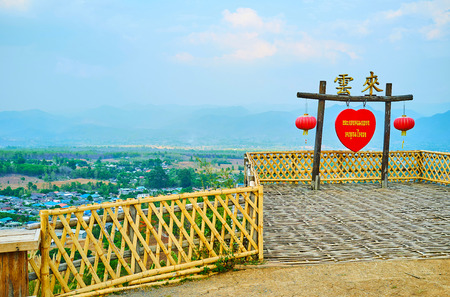 SANTICHON, THAILAND - MAY 5, 2019: Yun Lai viewpoint is decorated with wooden gate, Chinese red lanterns, red heart with Thai inscription and Chinese characters on the gates top, on May 5 in Santichon