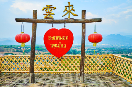 SANTICHON, THAILAND - MAY 5, 2019: The decorative gate of Yun Lai viewpoint with Thai sign on red heart, Chinese characters on the top and two scenic lanterns, on May 5 in Santichon