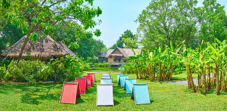 CHIANG MAI, THAILAND - MAY 5, 2019: Panorama of the Poopoopaper park with colorful panels of handmade paper, drying on the lawn among the banana palms and spread trees, on May 5 in Chiang Mai Редакционное