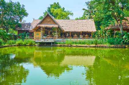 CHIANG MAI, THAILAND - MAY 5, 2019: The scenic pond in Poopoopaper park with a view on nipa hut, housing the local souvenir store and cafe, on May 5 in Chiang Mai Редакционное