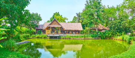 CHIANG MAI, THAILAND - MAY 5, 2019: Panorama of Poopoopaper park grounds with a pond, surrounded by spread trees and huts of souvenir store and cafe, on May 5 in Chiang Mai