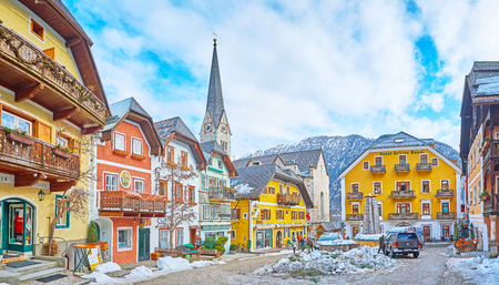 HALLSTATT, AUSTRIA - FEBRUARY 25, 2019: Panorama of Market square (Marktplatz) - the central town square with extant historical buildings and tall spire of Evangelical church, seen on background, on February 25 in Hallstatt. 報道画像