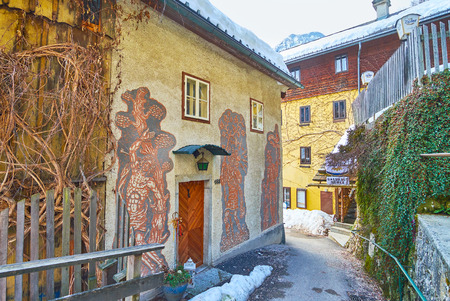 HALLSTATT, AUSTRIA - FEBRUARY 25, 2019: The narrow curved alley of Oberer Marktplatz with old houses, nowadays serving as hotels or stores, on February 25 in Hallstatt.