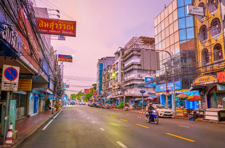 BANGKOK, THAILAND - MAY 16, 2019: The bright morning cloudy sky over the sleeping city with closed shops, cafes and massage salons, on May 16 in Bangkok, Thailand Редакционное