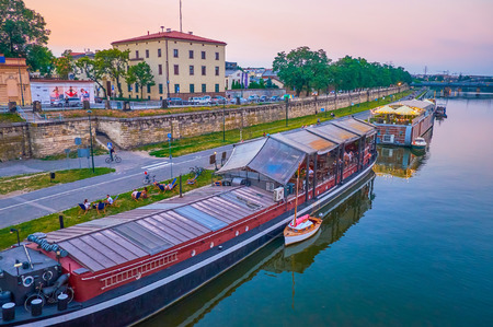 KRAKOW, POLAND - JUNE, 20, 2018: The large barges moored at the bank of Vistula river serves as the restaurants, also offer outdoor chairs on the grass at the rivers bank, on June 20 in Krakow Editorial