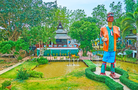 PAI, THAILAND - MAY 5, 2019: The metal statue of Karen tribe long neck woman in colorful clothes, standing among the small ponds in park of the countryside hotel, on May 5 in Pai Редакционное