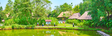 CHIANG MAI, THAILAND - MAY 5, 2019: Panorama of the scenic green lake bank in Poopoopaper park - eco-friendly museum-factory, of handmade paper producing of elephant poop, on May 5 in Chiang Mai