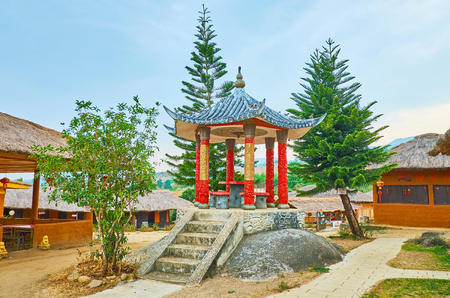 SANTICHON, THAILAND - MAY 5, 2019: The small pavilion with sweeping roof and carved red columns, standing on the pedestal in Chinese Cultural Center park, on May 5 in Santichon Редакционное