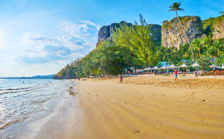 AO NANG, THAILAND - APRIL 25, 2019: The long tideline of Centara Grand beach with line of sunshades, lush tropical greenery and tall rocks on the background, on April 25 in Ao Nang