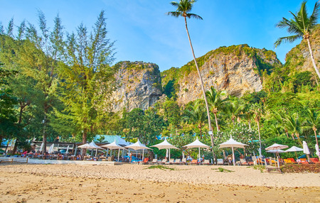AO NANG, THAILAND - APRIL 25, 2019: The line of sunbeds with umbrellas at the lush green garden of Centara Grand beach, surrounded by huge rocks, on April 25 in Ao Nang