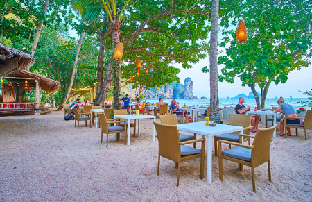 AO NANG, THAILAND - APRIL 25, 2019: Enjoy the dinner in coastal restaurant, hidden in shade of trees and overlooking the Tonsai Bay and Ao Nang Tower rock, on April 25 in Ao Nang