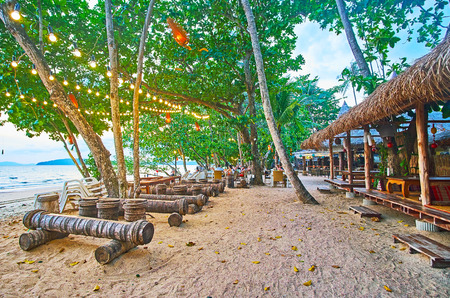 AO NANG, THAILAND - APRIL 25, 2019: The lush tropical greenery hides the wooden huts of beach cafes and bars with cozy open air terraces and lounge zones, on April 25 in Ao Nang Редакционное