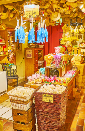 HALLSTATT, AUSTRIA - FEBRUARY 25, 2019: Interior of Salzkontor store with baskets, wooden boxes, display cabinets with heaps of different handmade soap and racks with hanging pieces of many shapes, on