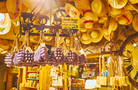 HALLSTATT, AUSTRIA - FEBRUARY 25, 2019: The classic interior of Salzkontor store, decorated with straw hats on ceiling and vintage racks with hanging massage scrub soap, on February 25 in Hallstatt