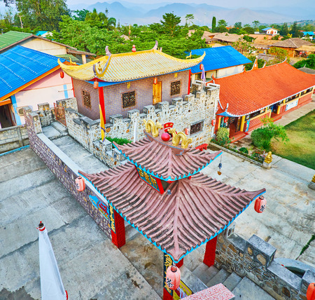 SANTICHON, THAILAND - MAY 5, 2019: The tile sweeping roofs of the fortress buildings in Chinese Cultural Center of tea village, on May 5 in Santichon