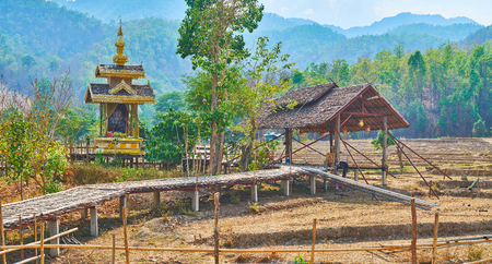 Walk through the curved Boon Ko Ku So bamboo bridge with shady pavilions, Buddhist shrine and dry agricultural lands around it, Pai, Thailand