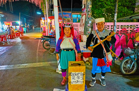 PAI, THAILAND - MAY 5, 2019: The couple of senior members of Lisu Hill Tribe in traditional costumes sings and dances, playing tseubeu banjo-like musical instrument in Walking Street, on May 5 in Pai