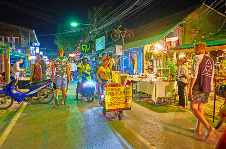 PAI, THAILAND - MAY 5, 2019: The crowded Night Market in Walking Street with many food and souvenir stalls, cafes, bars; the street vendor with cart offers home made coconut ice cream, on May 5 in Pai Редакционное